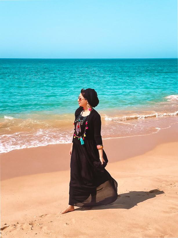 Muslim blogger walking on beach wearing black dress