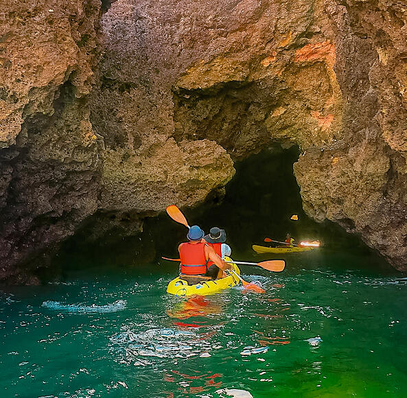 Muslim travel couple kayaking into dark cave