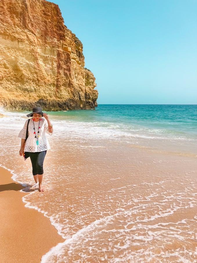 Muslim blogger on beach with cliffs