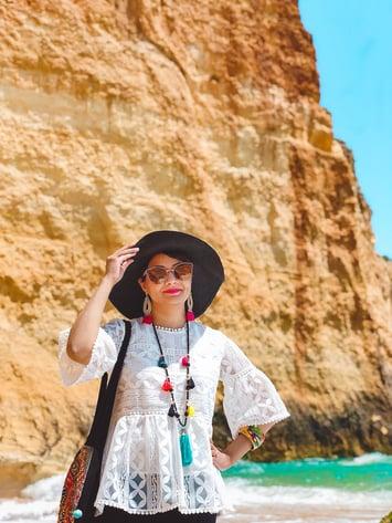 Muslim blogger wearing white shirt and black hat on beach