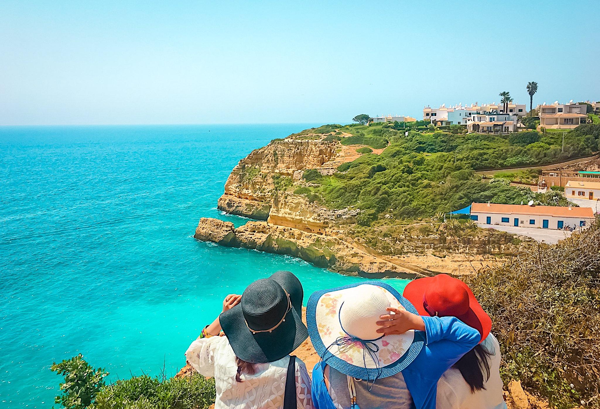 Muslim friends with floppy hats looking at Algarve beach