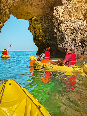 Friends on yellow kayak exiting cave