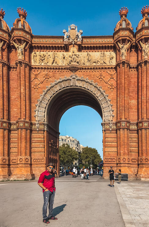 Muslim man wearing red shirt beside Arc de Triomf