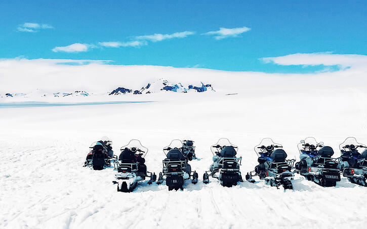 Snowmobiles parked on snow-covered glacier
