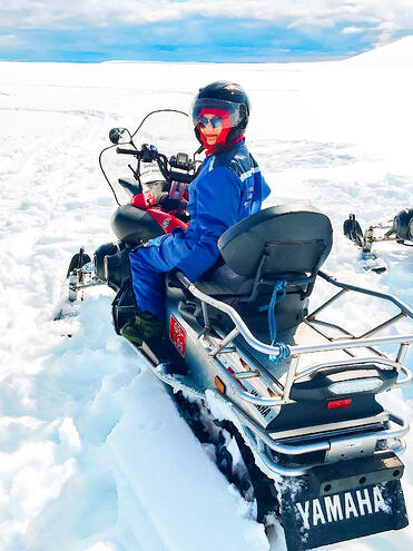Muslim travel blogger sitting on snowmobile on glacier