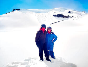 Muslim travel couple in snow suits on snowy glacier