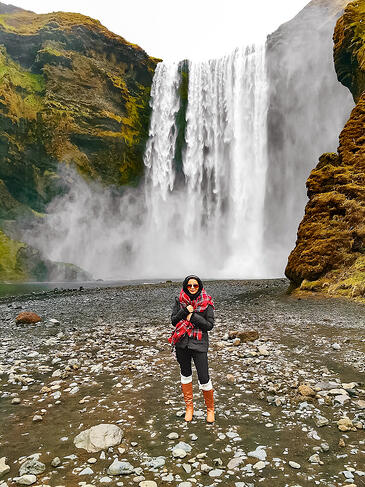 Muslim woman standing in front of Skogafoss waterfall