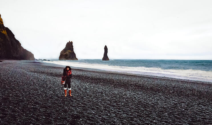 Woman alone on black sand beach with basalt sea rocks