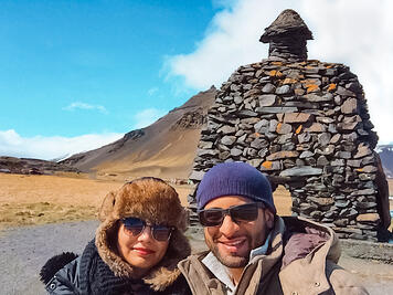Muslim travel couple in front of rock sculpture