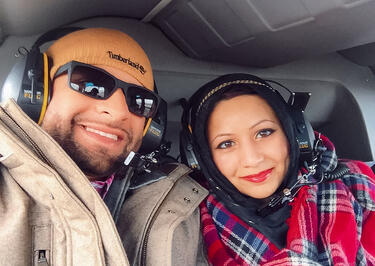 muslim travel couple on helicopter with headsets