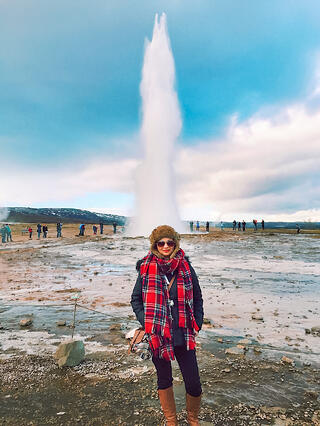 Woman wearing red scarf in front of erupting geyser