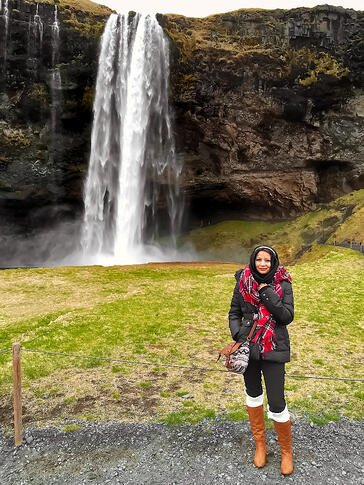 Muslim blogger wearing black jacket next to waterfall