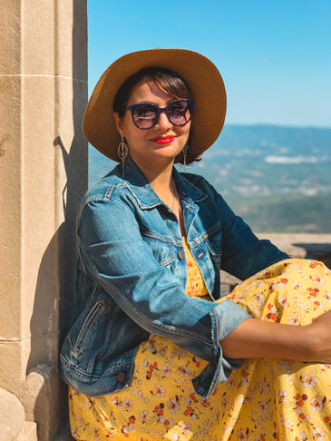 Muslim travel blogger in yellow dress sitting in arch on Montserrat