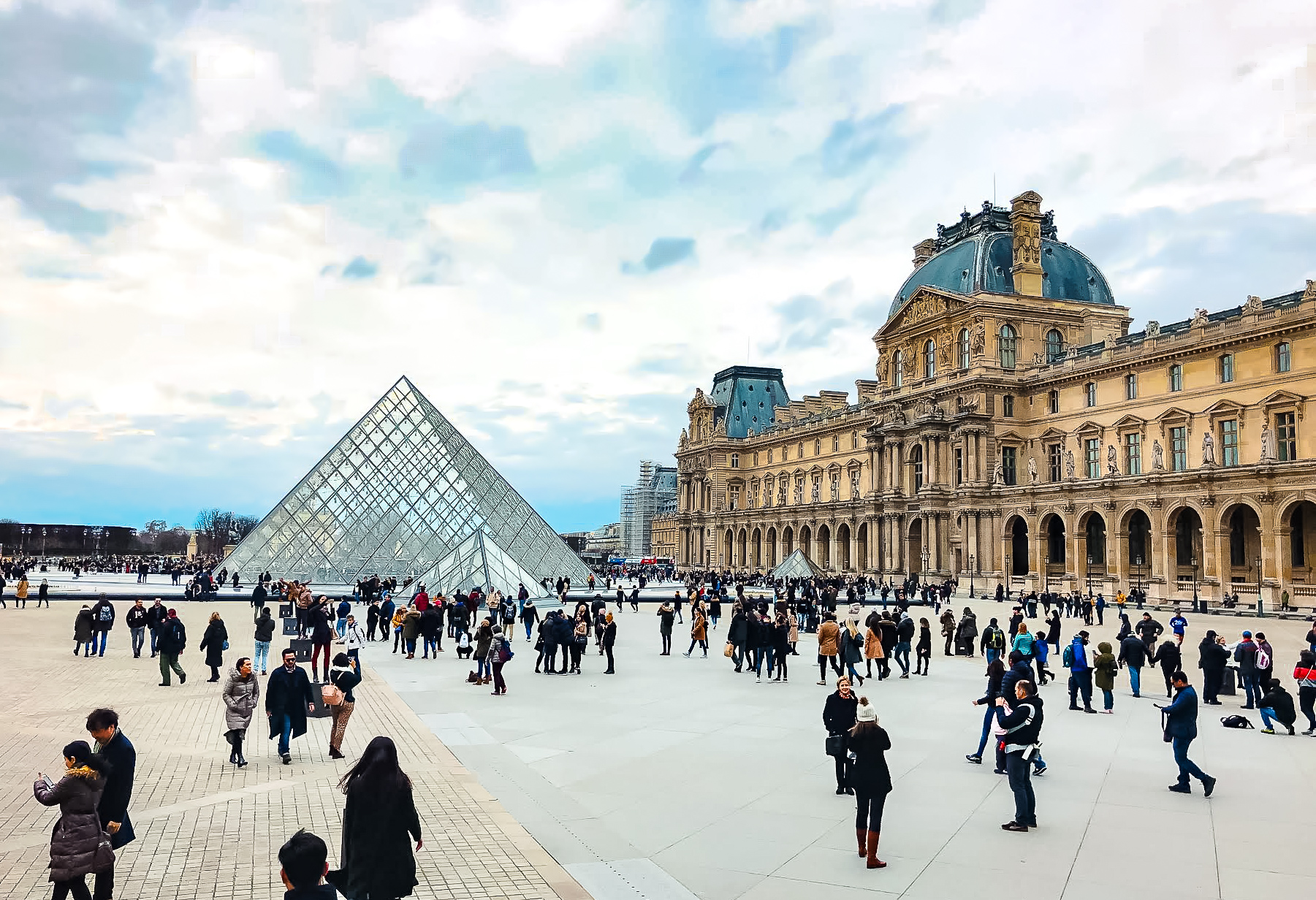 Louvre Museum's glass pyramid surrounded by people