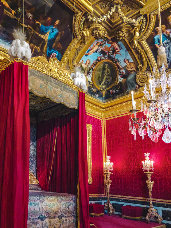 Four poster bed and mural ceiling inside Palace of Versailles
