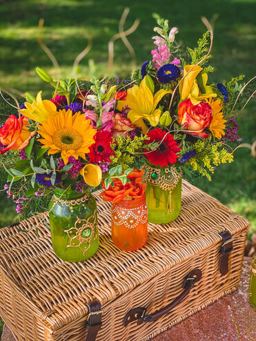 Colorful flowers inside mason jars with henna pattern