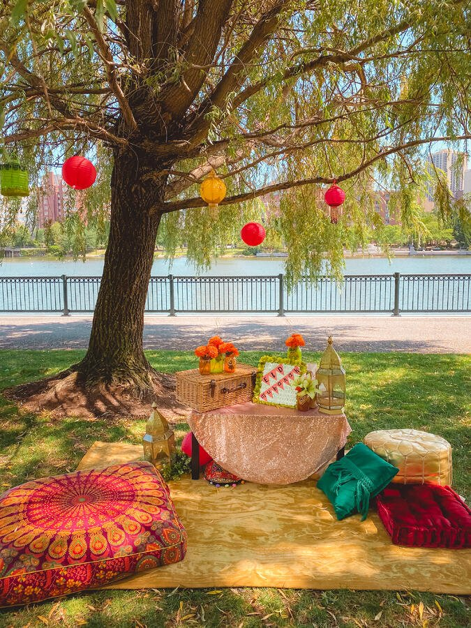 Outdoor Eid party decor with colorful cushions and lanterns