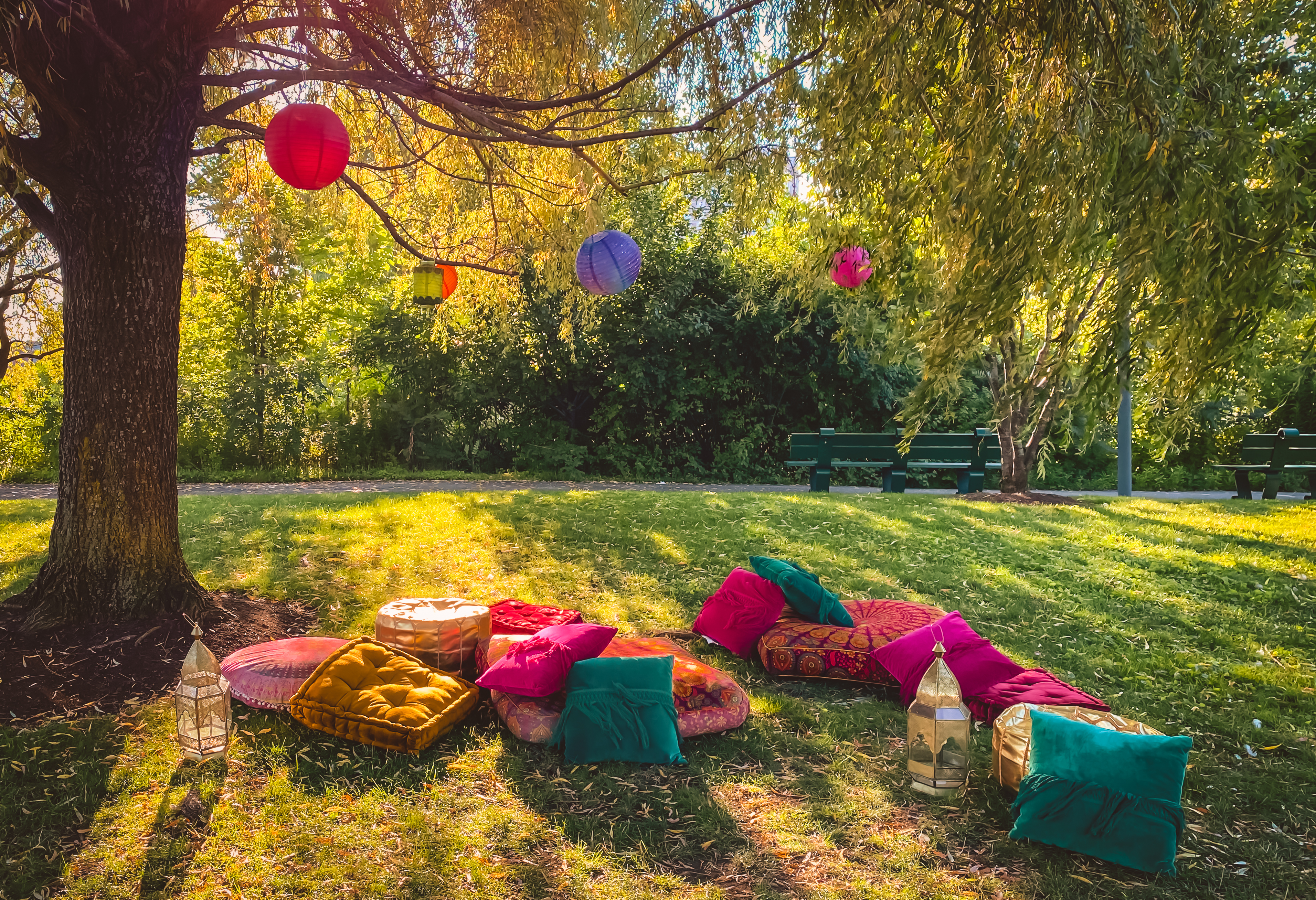 Colorful hanging lanterns and cushions in park for Eid