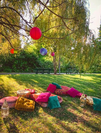 Colorful floor cushions strewn in park for Eid party